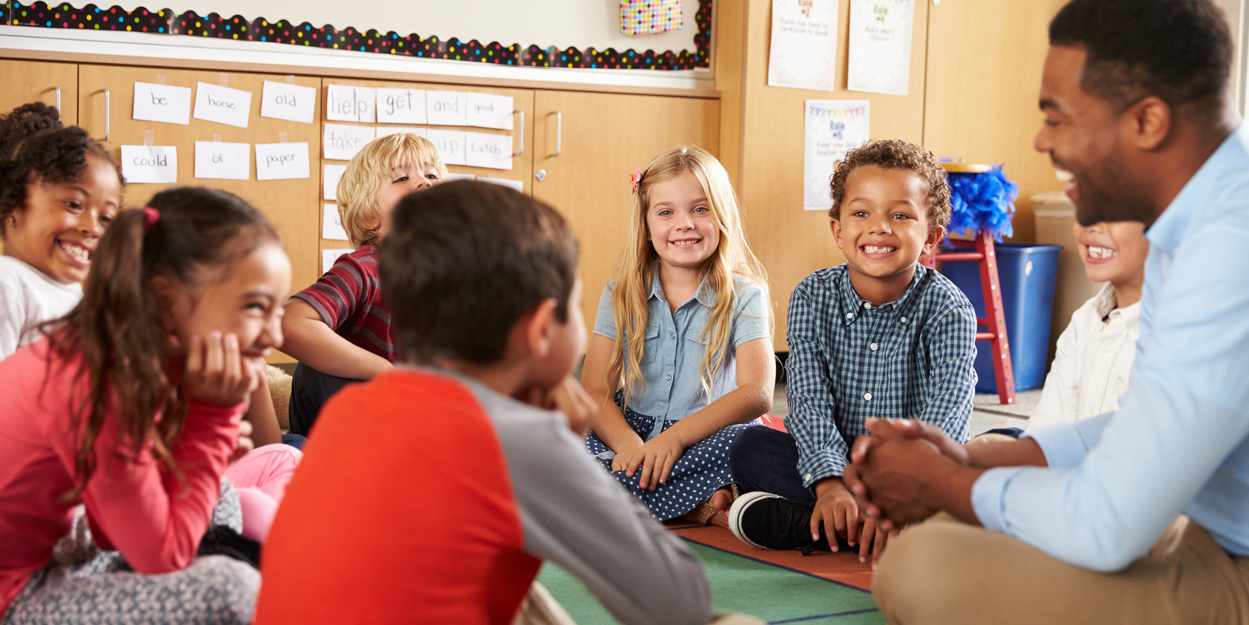 A teacher and students smiling and sitting cross legged in a circle