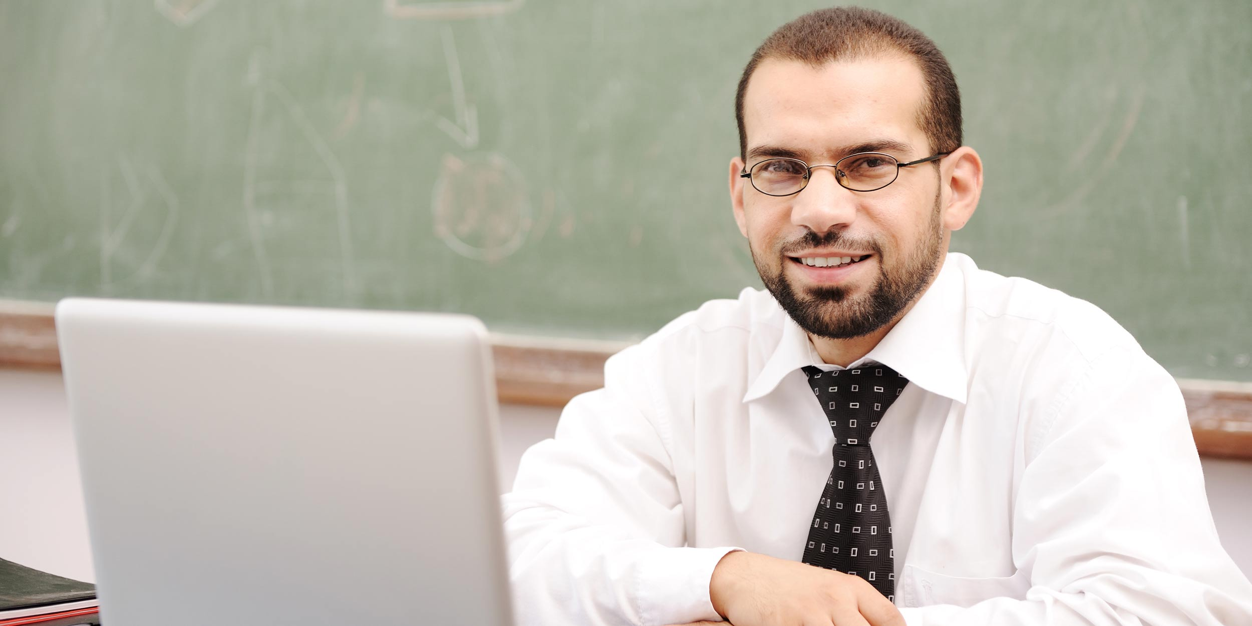 A man in a classroom sitting behind a laptop and smiling at the camera