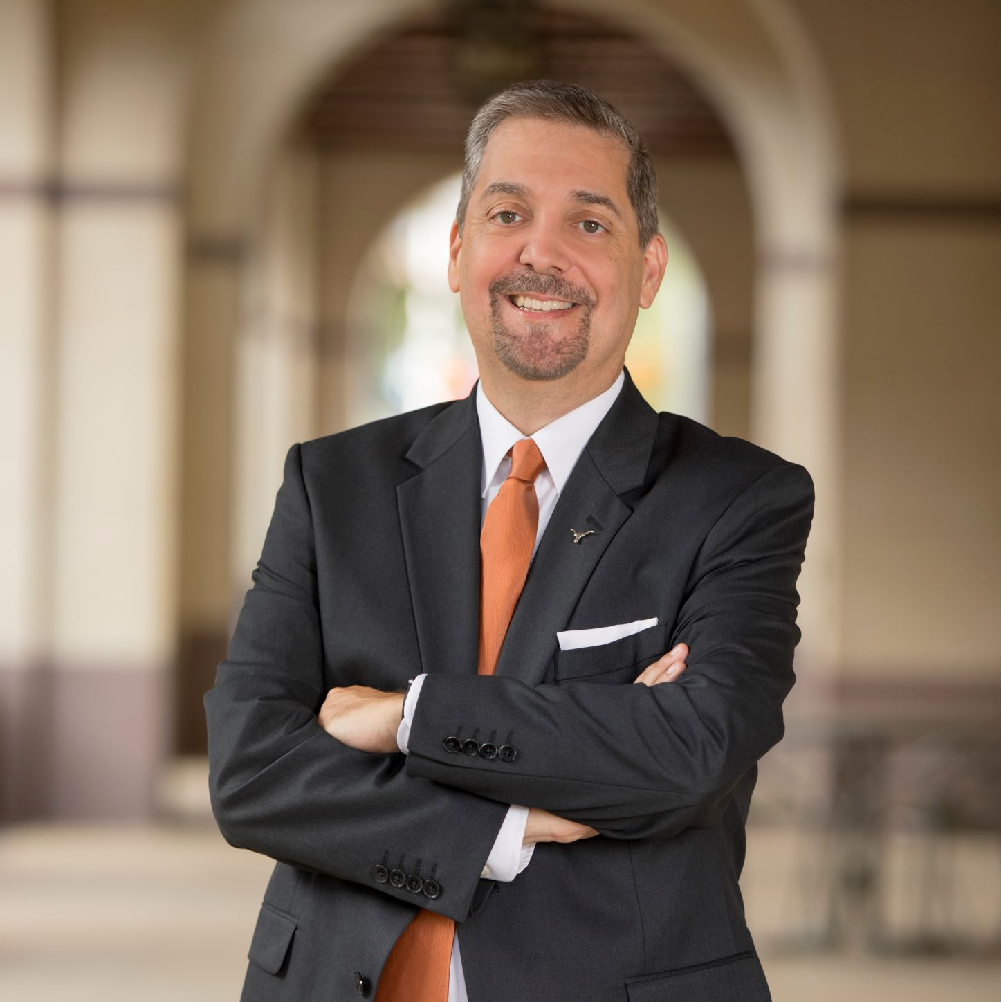 Charles Martinez in a suit with an orange tie.