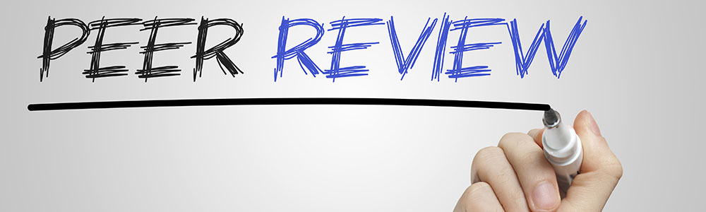 A hand writing 'Peer Review' on glass