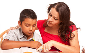 A student working in a book alongside a teacher