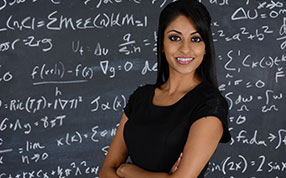 Woman standing in front of chalkboard with formulae written on it