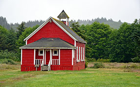 A red school house in a grassy field