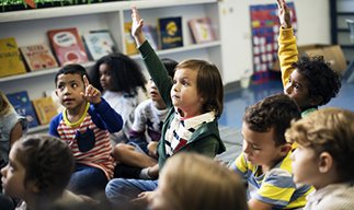Young children raising their hands in class
