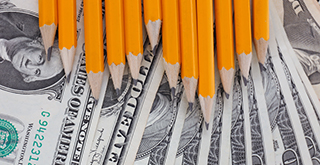 Pencils in the shape of a graph over money.