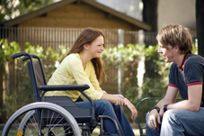 Girl in wheelchair talking with boy