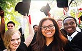 Vibrant photo of several students from diverse racial and ethnic backgrounds celebrating their college graduation.