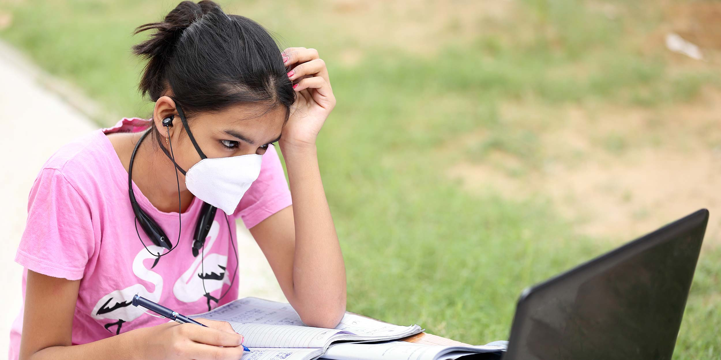 Photo of female student wearing a mask working outdoors on a laptop