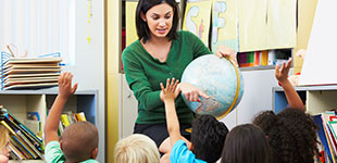 A teacher holding a globe and students with their hands raised